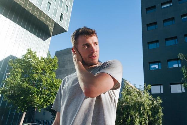 Homem bonito, cobrindo a orelha com a mão em pé na frente do edifício moderno
