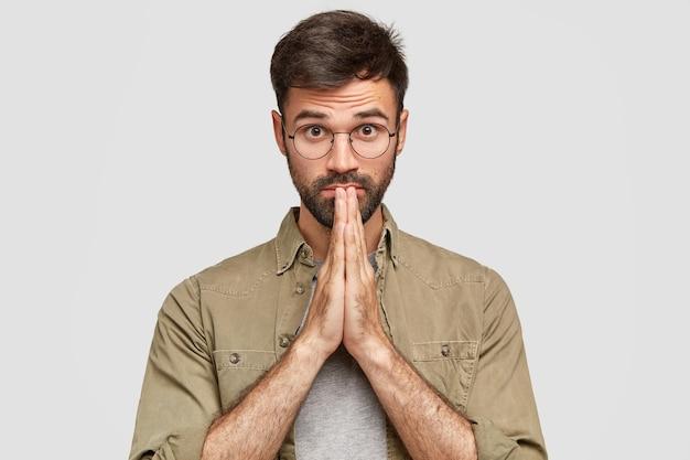 Homem bonito com a barba por fazer tem olhos cheios de fé, mantém as mãos juntas, ora por algo, tem expressão facial calma