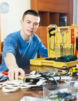Homem bonito com a caixa de ferramentas atingindo o martelo