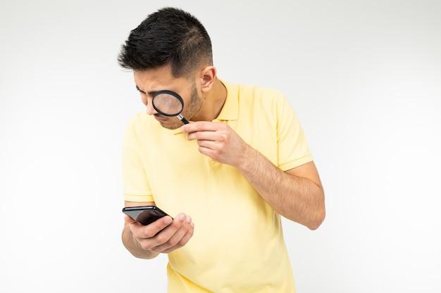 Homem bonito com baixa visão detém uma lupa e um smartphone na mão em um fundo branco com espaço de cópia