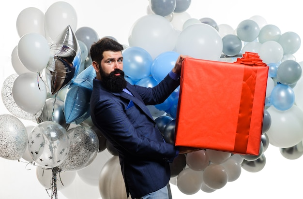 Homem bonito com balões de hélio e uma grande caixa de presente, festa de aniversário