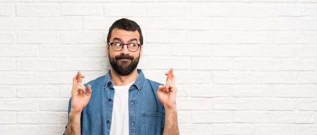 Homem bonito com barba ao longo da parede de tijolos brancos com dedos cruzando e desejando o melhor