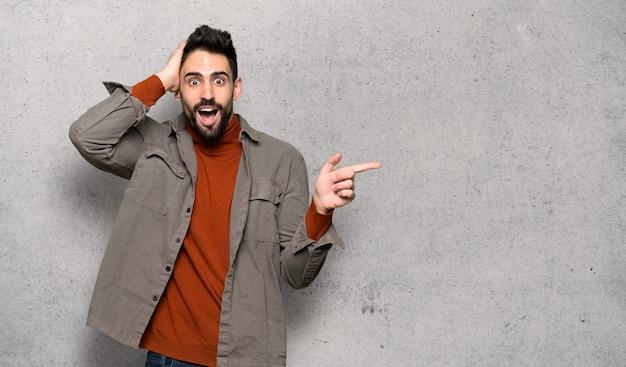 Homem bonito com barba apontando o dedo para o lado e apresentando um produto sobre a parede texturizada