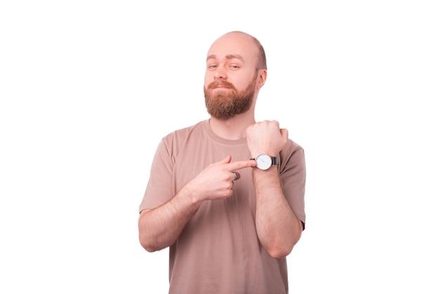 Homem bonito com barba apontando para um relógio