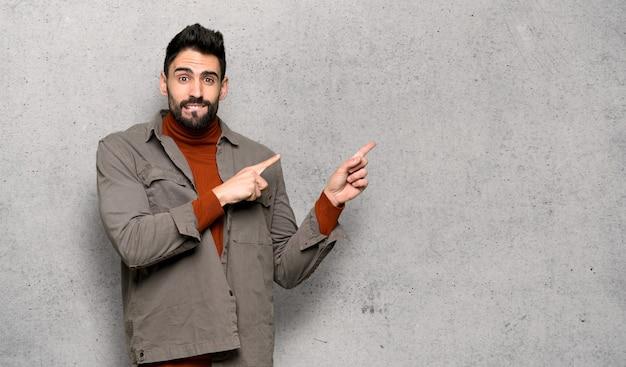 Homem bonito com barba assustada e apontando para o lado sobre a parede texturizada