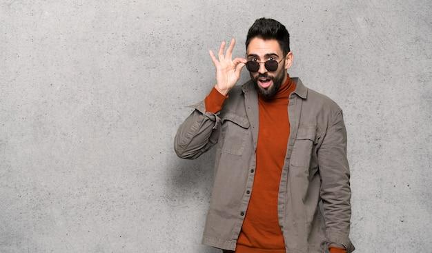 Homem bonito com barba com óculos e surpreso ao longo da parede texturizada