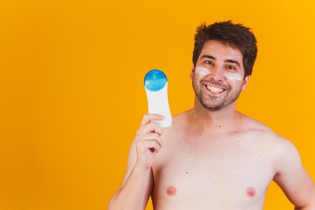 Homem bonito com barba de férias, vestindo maiô, segurando um frasco de protetor solar