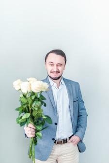 Homem bonito com barba de pé contra um fundo cinza com um buquê de rosas brancas