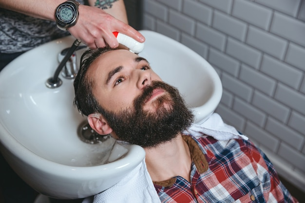 Homem bonito com barba e camisa quadriculada fazendo lavagem de cabelo por cabeleireiro em salão de cabeleireiro