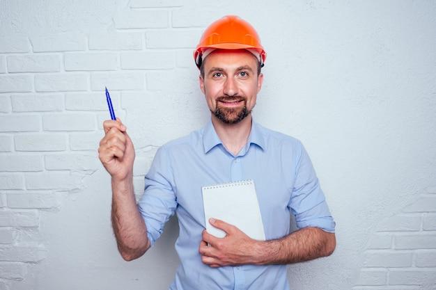 Homem bonito com barba e capacete de segurança no fundo de um construtor de parede de tijolos brancos segurando um caderno