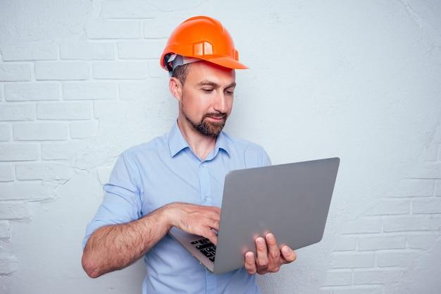 Homem bonito com barba e capacete em um fundo de um construtor de parede de tijolos brancos segurando um laptop na compra online de materiais de construção