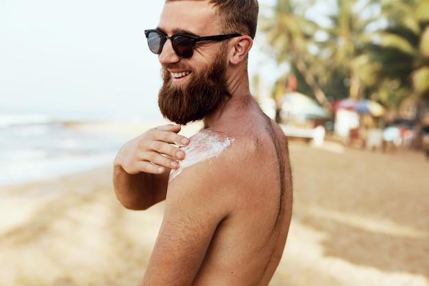 Homem bonito com barba, em óculos de sol, tomando banho de sol com loção de protetor solar no corpo no verão. bronzeamento artificial masculino usando creme de bloco solar