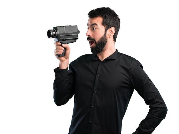 Homem bonito com barba filmando no fundo branco