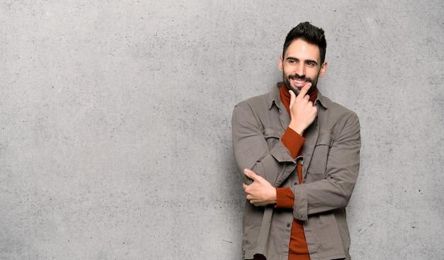 Homem bonito, com barba, olhando para o lado com a mão no queixo sobre a parede texturizada