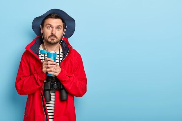 Homem bonito com barba por fazer e bigode faz expedição, para para descansar, bebe café da garrafa térmica, tem expressão surpresa, usa binóculos para explorar os arredores, usa jaqueta vermelha e chapéu