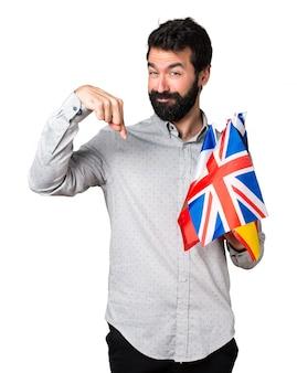 Homem bonito com barba segurando muitas bandeiras e apontando para baixo