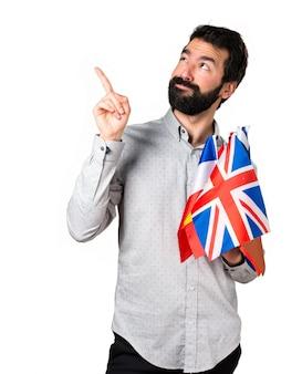 Homem bonito com barba segurando muitas bandeiras e apontando para cima