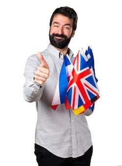 Homem bonito com barba segurando muitas bandeiras e com o polegar para cima