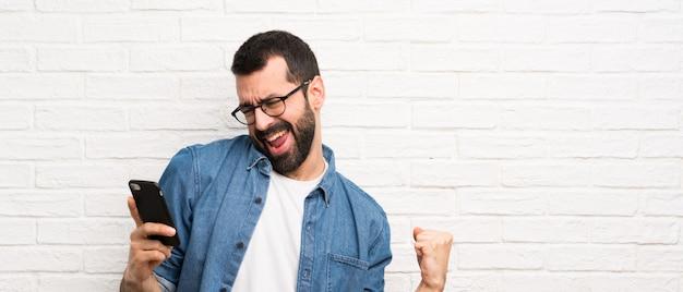 Homem bonito com barba sobre parede de tijolo branco com telefone em posição de vitória