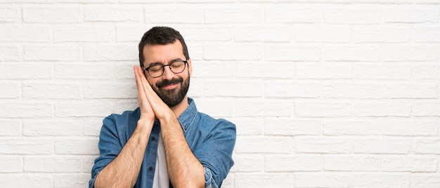 Homem bonito com barba sobre parede de tijolo branco, fazendo o gesto do sono em expressão dorable
