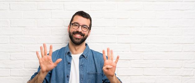 Homem bonito com barba sobre parede de tijolos brancos, contando nove com os dedos