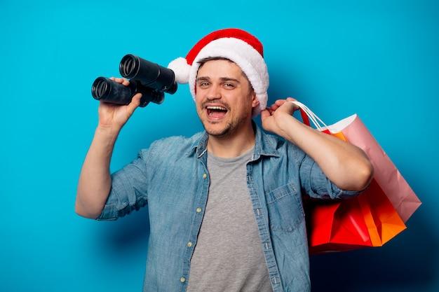 Homem bonito com binóculos e sacolas de compras