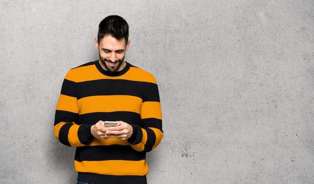 Homem bonito com blusa listrada, enviando uma mensagem com o celular sobre a parede texturizada
