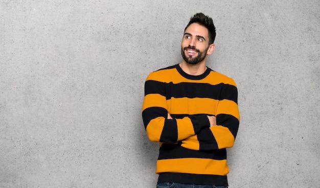 Homem bonito com blusa listrada, olhando para cima, enquanto sorrindo sobre a parede texturizada
