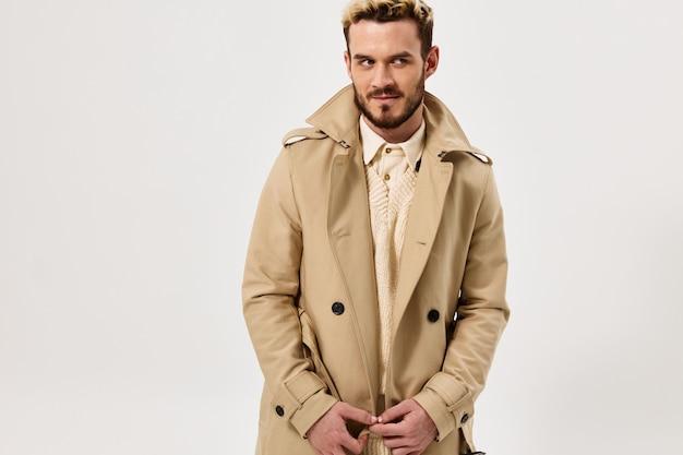 Homem bonito com cabelo cheio em um casaco estilo outono estúdio estilo moderno