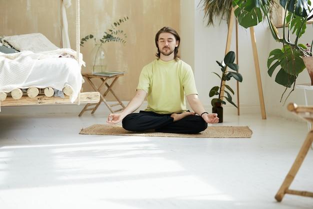 Homem bonito com cabelo comprido meditando em pose de lótus, bela pessoa aprendendo a ter atenção plena em casa