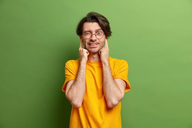 Homem bonito com cabelo escuro tapando as orelhas piscando os olhos evitando som alto