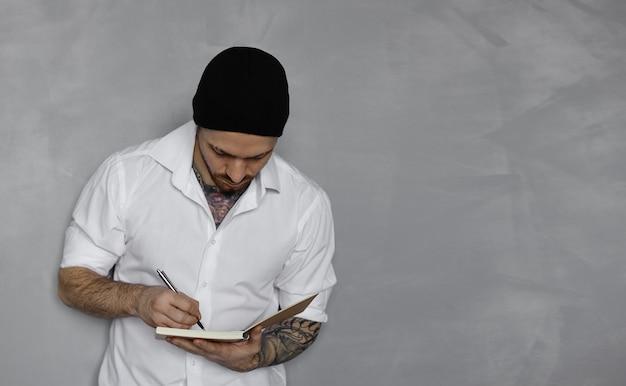 Homem bonito com camisa branca e chapéu preto fica perto da parede cinza e escreve notas no bloco de notas