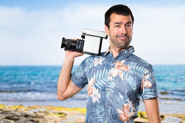Homem bonito com camisa de flores filmando na praia