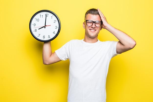 Homem bonito com camiseta branca e óculos transparentes segurando um grande relógio em uma das mãos