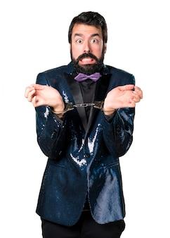 Homem bonito com casaco de lantejoulas com algemas