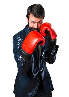 Homem bonito com casaco de lantejoulas com luvas de boxe