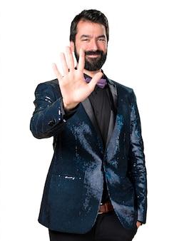 Homem bonito com casaco de sequin contando cinco
