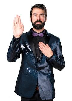 Homem bonito com casaco de sequin fazendo um juramento