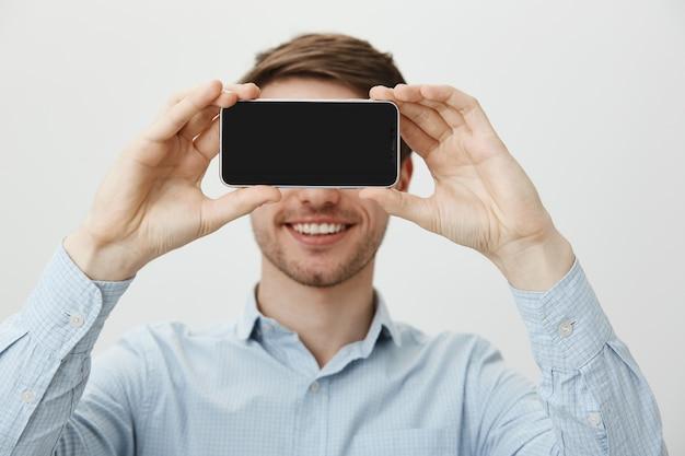 Homem bonito com cerdas, sorrindo mostrando a tela do smartphone