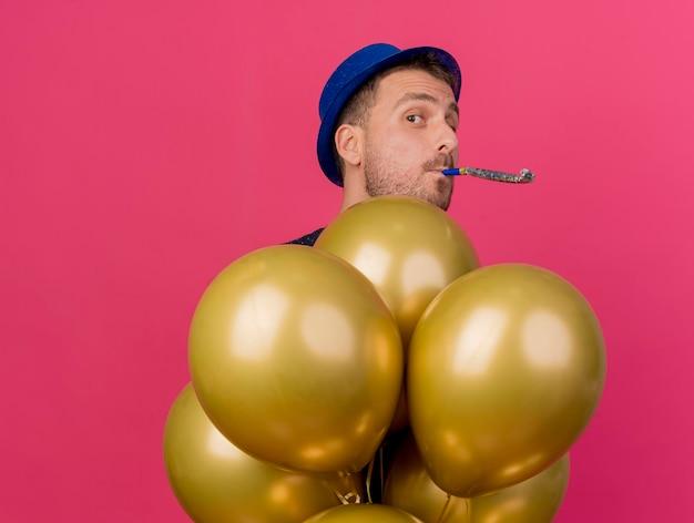 Homem bonito, com chapéu de festa azul, segurando balões de hélio, soprando apito isolado na parede rosa com espaço de cópia