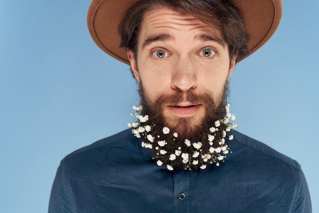 Homem bonito com chapéu de flores na cidade charme closeup emoções fundo azul
