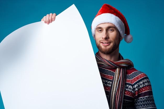 Homem bonito com chapéu de papai noel segurando uma bandeira de fundo azul de férias