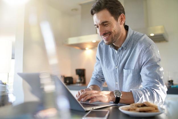 Homem bonito com computador na cozinha moderna
