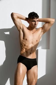Homem bonito com corpo musculoso e calcinha preta com luz de fundo
