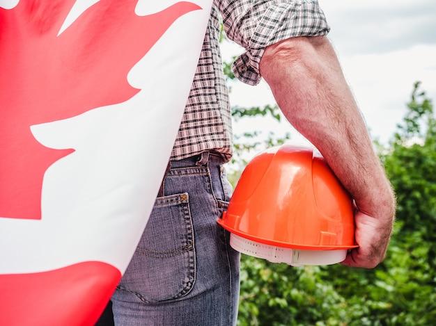 Homem bonito com ferramentas, segurando uma bandeira americana
