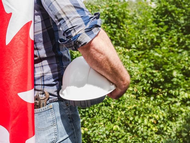 Homem bonito com ferramentas, segurando uma bandeira do canadá