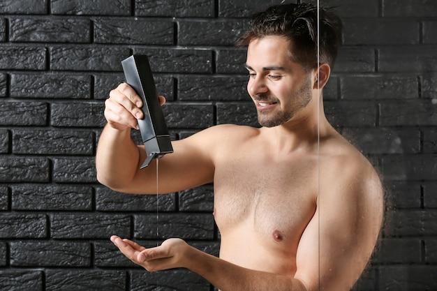 Homem bonito com frasco de shampoo no escuro