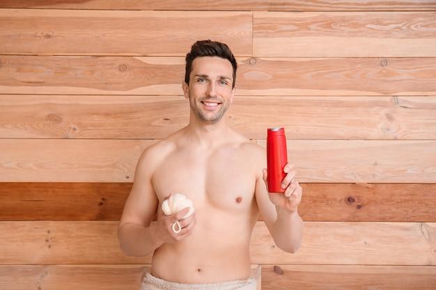 Homem bonito com gel de banho e bucha de madeira