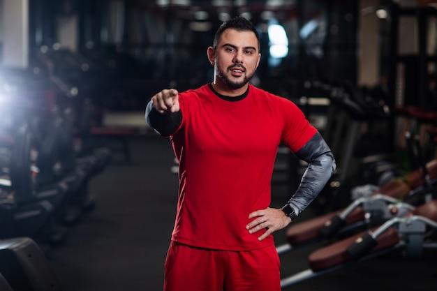 Homem bonito com grandes músculos, posando para a câmera no ginásio