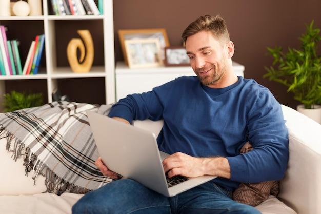 Homem bonito com laptop contemporâneo em casa